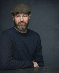 Professional portrait of a man against a blue background